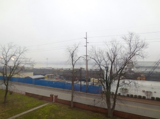 Across the street is Jeffboat, the modern shipyard on the site of the old Howard Shipyard. Several barges, in varying stages of completion, can be seen.
