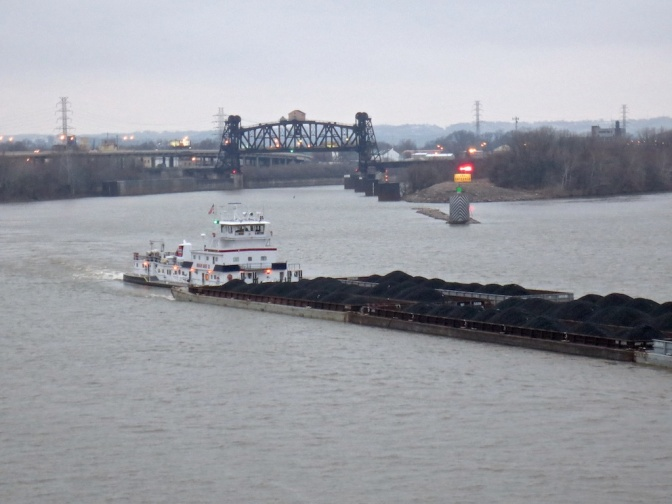An Ingram Barge Company towboat pushes a coal tow out of the Portland Canal and past Louisville.