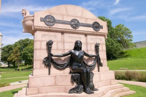 """The Naked Truth"" sculpture, built in 1914 to honor three German newspaper editors and St. Louis' German heritage in general. Adolphus Busch was one of the major funders of the statue. According to a brochure of the Water Tower and Park Preservation Society, the sculpture was created ""in bronze rather than white marble to minimize the nudity."""